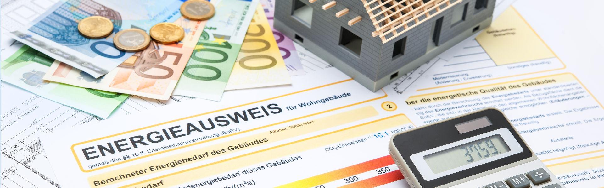 Energieausweis und Betriebskostenabrechnung auf einem Tisch mit Geld, einem Taschenrechner und einem Modellhaus - HWA-Frenzel