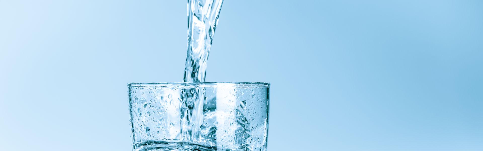 Wasser, welches in ein Glas gegossen wird. - HWA-Frenzel