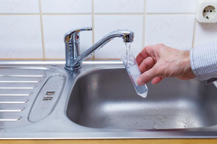Abbildung davon wie jemand Wasser aus einem Wasserhahn in ein Reagenzglas füllt. - HWA-Frenzel